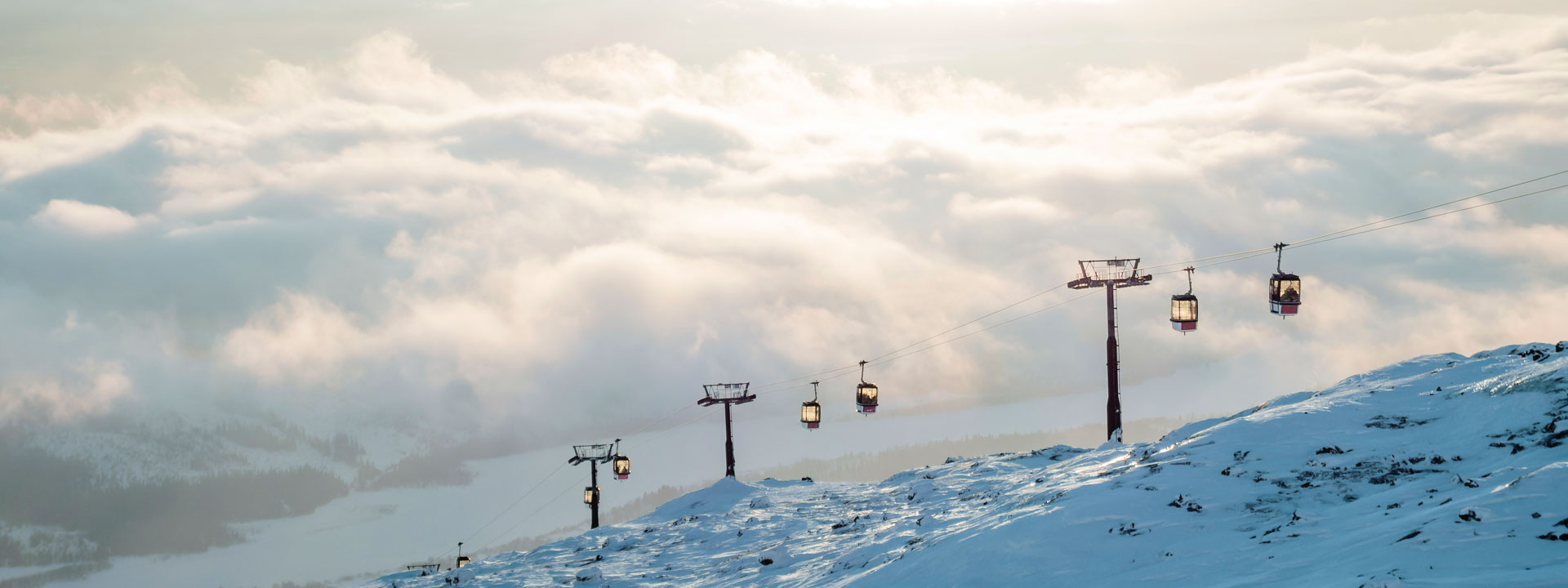 Ski lift with mountains and clouds in the background