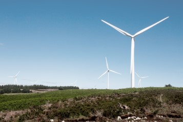 Image of a wind turbine located on a hill, in a green landscape with blue skies above.