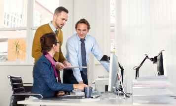 Three coworkers looking at a computer screen at a desk