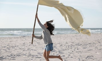 A girl running on a beach with a flag