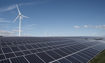 Image of solar panels in front of a wind turbine.