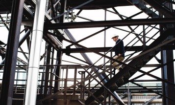 An employee at a power plant walking down stairs