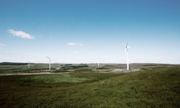 Photo of wind turbines located in a green landscape, with blue skies above.