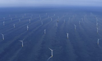 Image of rows of wind turbines located in the blue ocean.