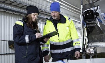 A female and a male employee checking a clipboard