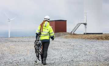 Image of a Vattenfall employee wearing safety clothes and helmet, walking across dry ground towards a wind turbine.