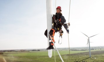 Image of a female Vattenfall worker hanging in a safety rope on the side of a wind turbine.