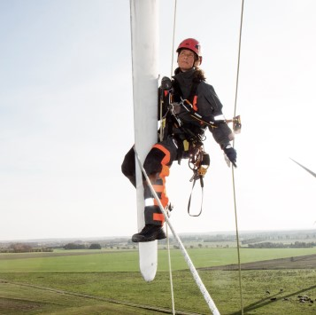 Woman hanging on a wind turbine