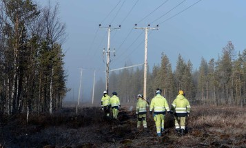 Workers walking below power lines in Northern Sweden
