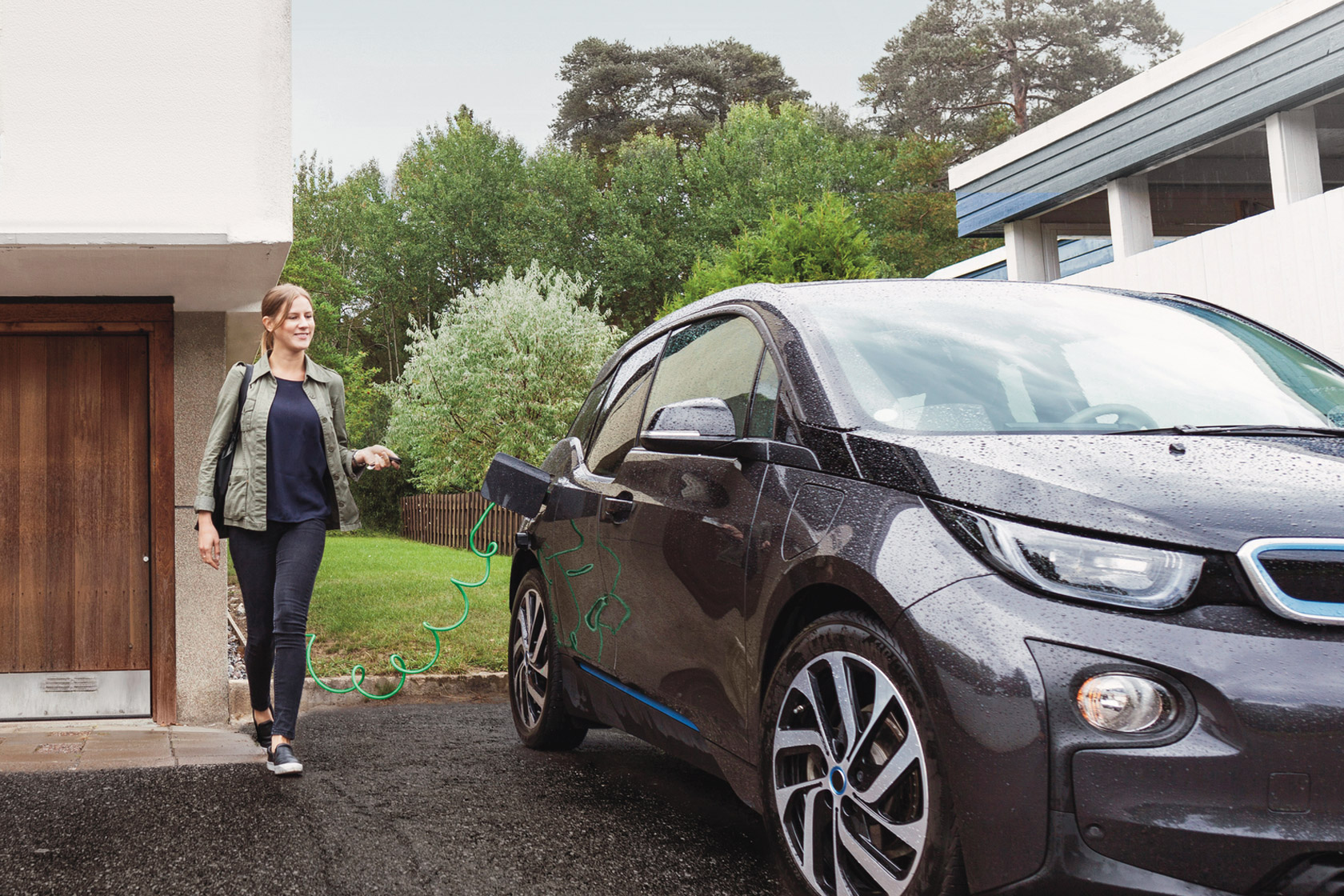 A woman walking towards her electric car