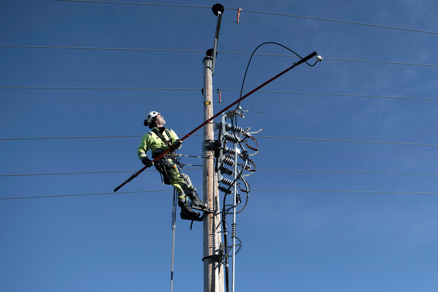 Employee in safety gear working on top of electricity pylon