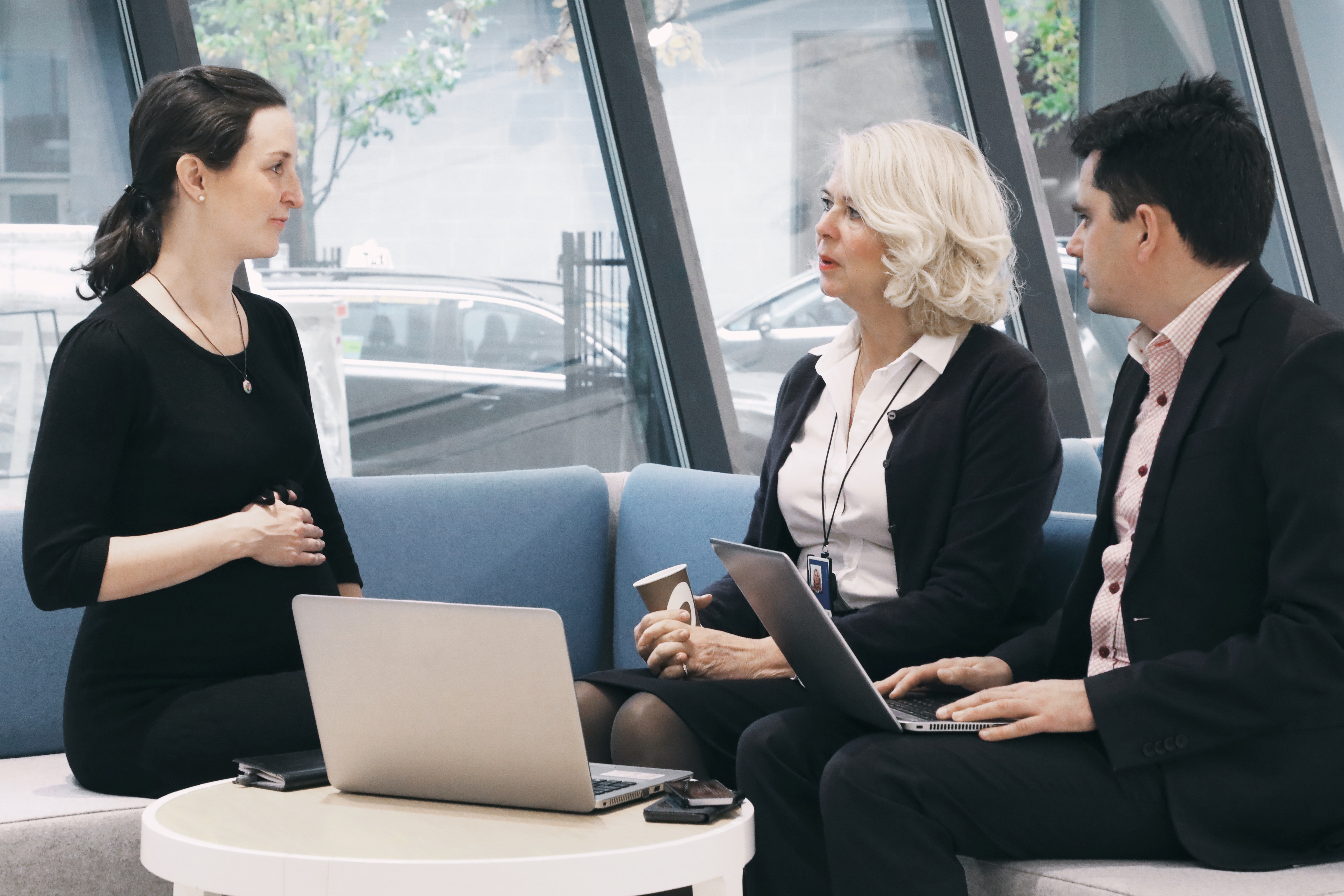 A pregnant employee talking to two colleagues