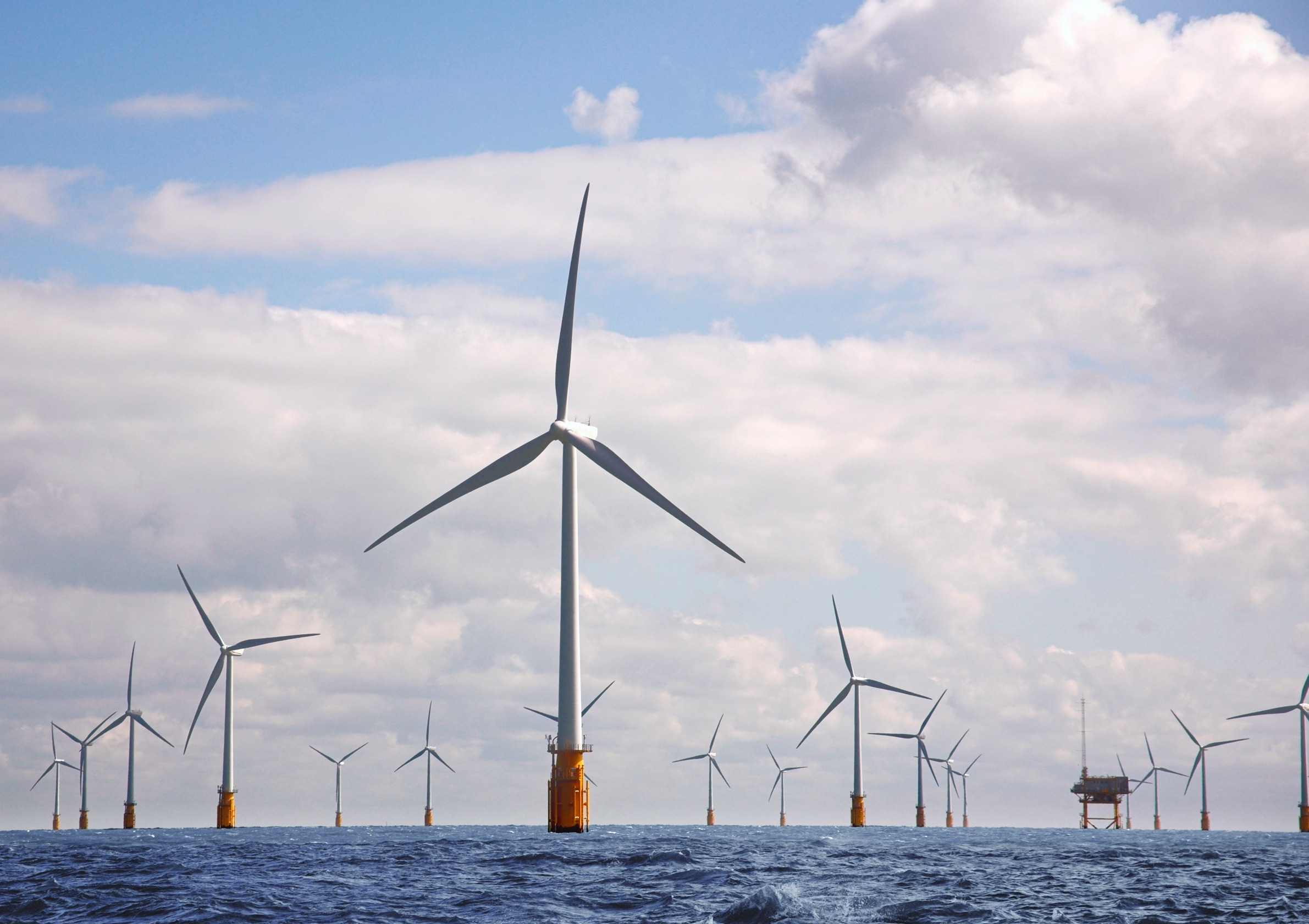 Image of wind turbines located in the sea, with one great wind turbine in the center of the image. Blue skies and blue water.